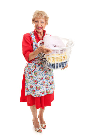 70s adult: Senior woman dressed in retro fashion carrying a basket of laundry.  Full body isolated.