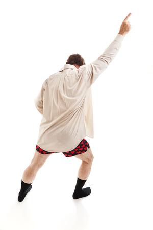 Man van middelbare leeftijd dansen rond in zijn sokken, shirt, en ondergoed, zingen oude tijd rock & roll nummers. Geïsoleerd op wit.