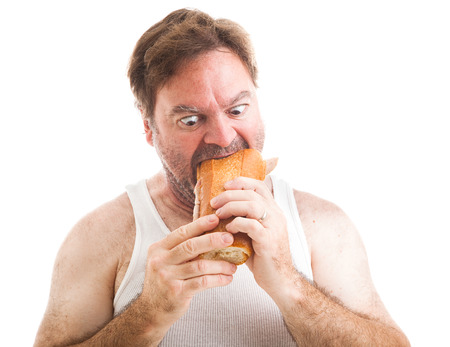 hoagie: Humorous photo of a scruffy unshaven man in his undershirt, eating a big submarine hoagie sandwich.  Isolated on white.