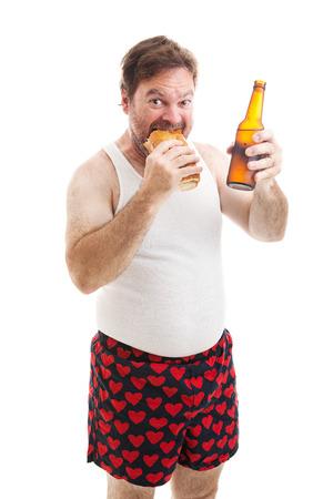 wifebeater: Scruffy, sovrappeso uomo di mezza et� in mutande, mangiando un panino sottomarino e bere una birra. Isolati su bianco. Archivio Fotografico
