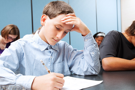 Adolescent middle school boy concentrats on a standardized test in school.