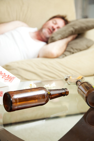 wifebeater: Man asleep on the couch with ashtray, takeout food container, and beer bottles on coffee table.  Shallow Depth of field with focus on beer bottles.   Stock Photo