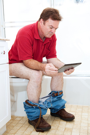 toilet: Man reading a tablet pc while using the toilet in the bathroom. Stock Photo