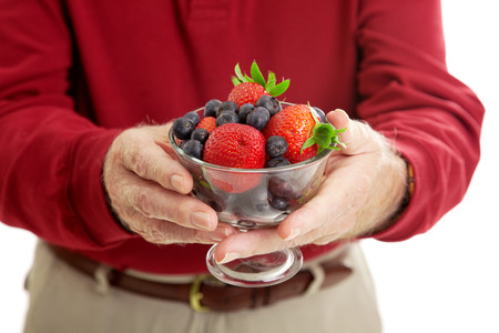 Closeup of senior man's hands holding a bowl of healthy, antioxidant rich berries. Stock Photo - 28559536