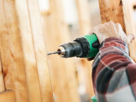 建設現場でドリルを使用して、大工の手のクローズ アップ。ドリルと手に焦点を当てます。フィールドの浅い深さ。