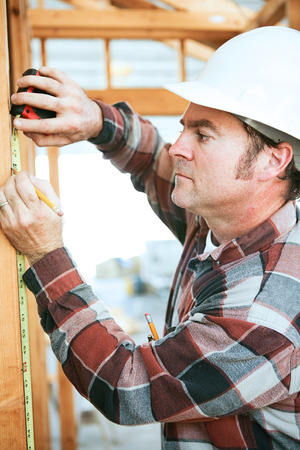 building contractor: Construction worker taking measurements on the job site.