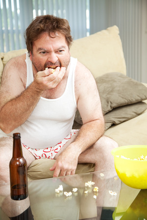 couch: Middle aged man at home on the couch watching tv, drinking beer, and eating popcorn, in his underwear.