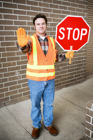 hand guard: Handsome school crossing guard holding a stop sign.   Stock Photo
