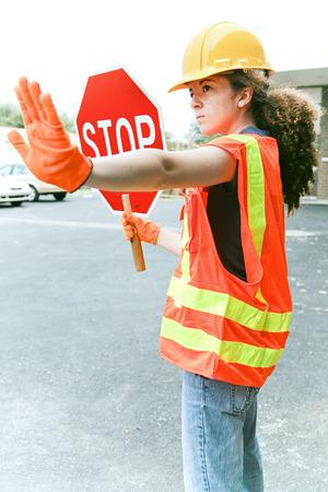 若い女性建設見習い一時停止の標識を保持していると、トラフィックを誘導します。 写真素材