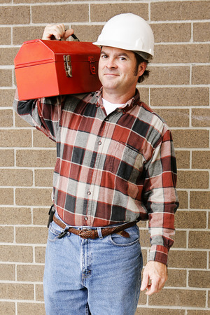 Handsome repairman carries his tool box on his shoulder.   photo