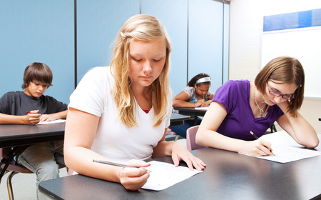 Pretty blond girl taking a test with her high school class.   photo