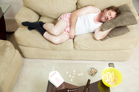 Overhead view of an unemployed man sleeping on the couch in his underwear, with food, beer, and cigarettes on the coffee table.   Foto de archivo