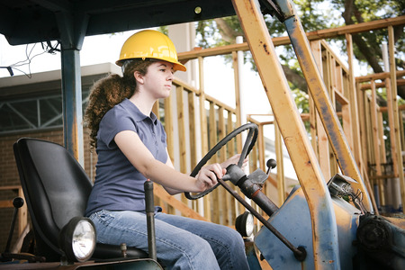 jobsite: Young female construction apprentice learning to drive heavy equipment.   Stock Photo