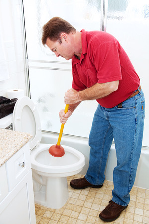 Man in his bathroom unclogging a toilet with a plunger.   photo