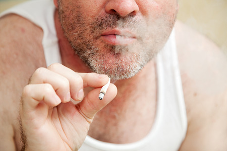 wifebeater: Closeup of a man smoking a joint and blowing smoke.   Stock Photo