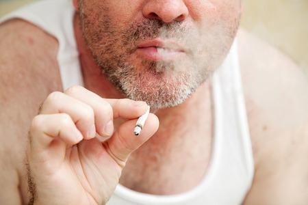 wifebeater: Primo piano di un uomo che fuma una sigaretta congiunta e soffiaggio.