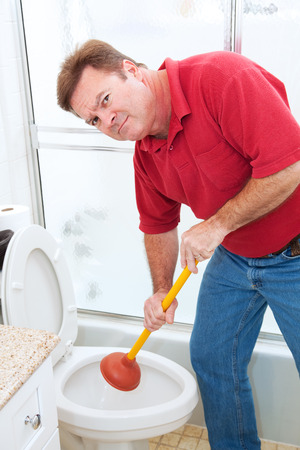 Man using a plunger to unclog a bathroom toilet.   photo
