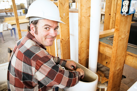 Plumber installing a toilet in a home which is under construction.   photo