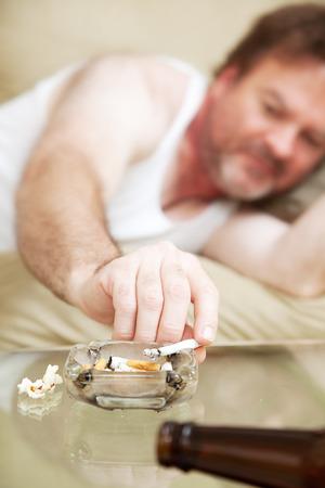 wifebeater: Middle invecchiato uomo disteso sul divano e il fumo di marijuana. Archivio Fotografico