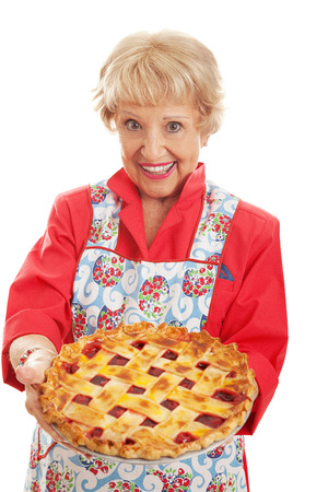Sweet retro style grandmother holding a delicious home baked cherry pie with lattice top crust.  Isolated on white.   photo
