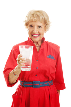 inflamation: Pretty senior woman drinking a large glass of ice water.  Isolated on white.