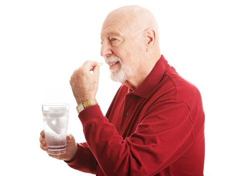 personas tomando agua: Hombre mayor hermoso que se mantiene saludable por tomar un suplemento de aceite de pescado con un vaso de agua. Aislado en blanco.