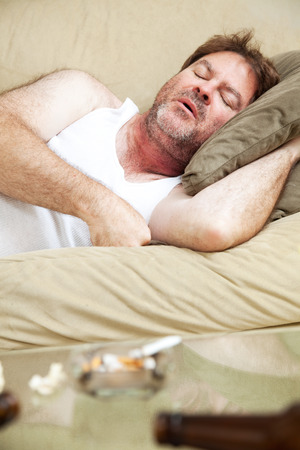 wifebeater: Middle aged man sleeping of a night of drinking and getting high.   Stock Photo