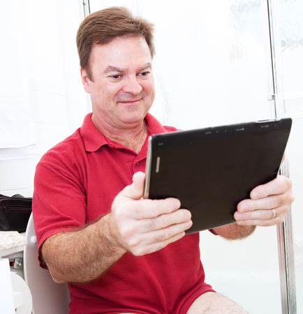 bowel movement: Man reading a tablet pc while using the bathroom. Stock Photo