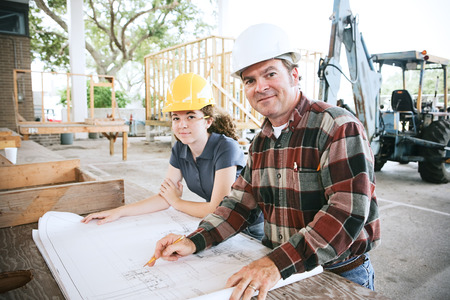 architect tools: Engineer going over blueprints with a student on the construction site.