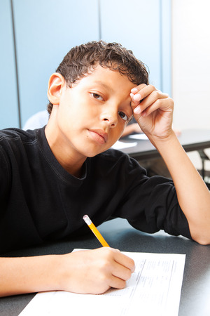 Teen boy worried about taking a standardized test.   photo
