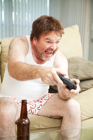 Middle aged man in his underwear playing video games and drinking beer.   Stock Photo