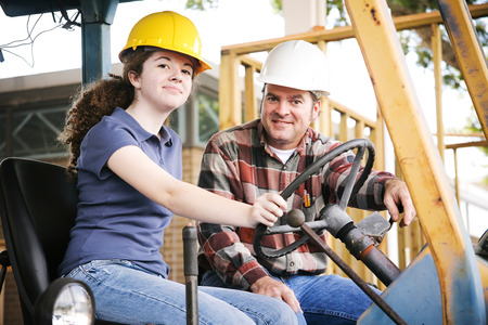 Vocational instructor teaching a young construction apprentice how to drive heavy equipment.   photo