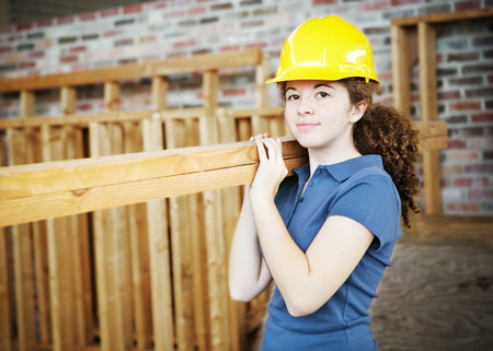 Young female apprentice carrying boards on a construction site.   photo