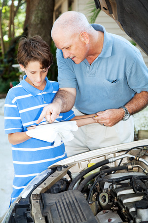Father teaching his son how to check the oil on the family car.   photo