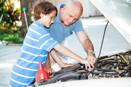 Father showing his son how to check the engine of the family car.   photo