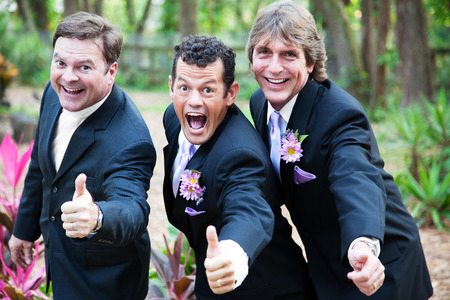 Two grooms and their minister giving a thumbs up at their gay wedding.   photo