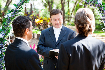 wedding vows: Minister performing marriage ceremony for two grooms at a gay wedding.