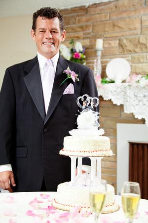 boda gay: Novio hermoso que se coloca al lado de la torta de la boda en su boda gay, esperando a su marido.