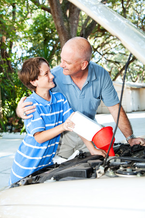 Father teaching his son how to put oil in the family car.   photo