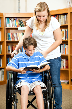 Disabled boy with a friend reading a book in the library.