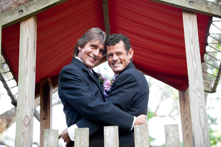 Newly married gay couple embracing under an outdoor canopy.   photo