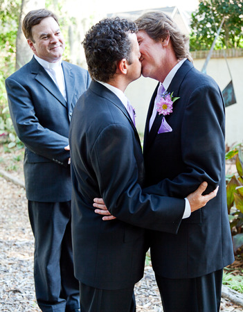 Two grooms kiss eachother in front of the minister at their gay marriage ceremony.  photo