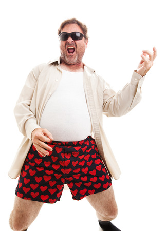 air guitar: Middle aged man playing air guitar in his underwear.  Isolated on white.  Stock Photo