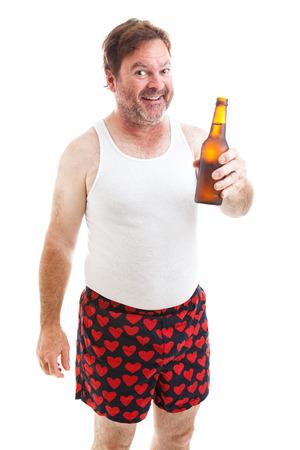 hombre tomando cerveza: Desaliñado hombre de mediana edad en su ropa interior que le ofrece una botella de cerveza. Aislado en blanco.