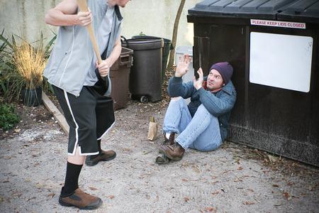 hombre pobre: Varón joven matón amenaza con golpear a un hombre sin hogar con un bate de béisbol.