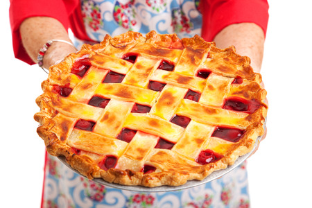 stereotypical: Closeup of a homemade cherry pie being held by a stereotypical grandma.  Isolated on white.