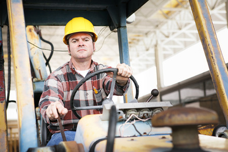 heavy equipment operator: Worker driving heavy construction equipment - bulldozer or backhoe.