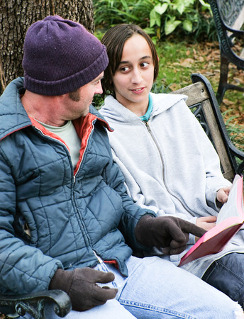 missionary: Homeless father and son reading the Bible, or a teen volunteer ministering to the poor.