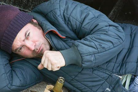 Homeless man sleeping on the ground in the cold with a cough. Stock Photo - 30452406