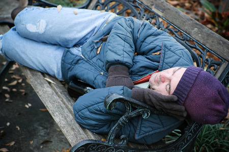 Homeless man asleep on a park bench with a bottle of wine.   photo
